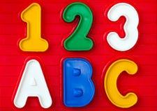Farbige Buchstaben und Zahlen auf einem roten Hintergrund Stockfotografie