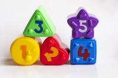 Bunte Plastikformen mit Zahlen auf einem weißen Hintergrund Stockfoto