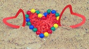 Bunte Plastikperlen und Herz vom roten Papier lizenzfreies stockfoto