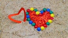 Bunte Plastikperlen und Herz vom roten Papier auf Herz-förmigem lizenzfreies stockfoto