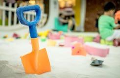 Bunte Plastikschaufel für Kinder im Sandkasten Lizenzfreie Stockbilder