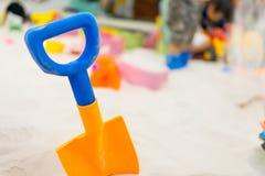 Bunte Plastikschaufel für Kinder im Sandkasten Stockfotografie