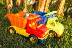 Bunte Plastikspielzeuglastwagen im Gras lizenzfreies stockfoto