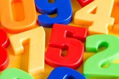 Bunte Plastikzahlen auf einem Holztisch Lizenzfreies Stockfoto