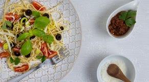 Bunte Platte von Spaghettis mit Tomaten, Oliven und frischen Kräutern Lizenzfreie Stockfotos