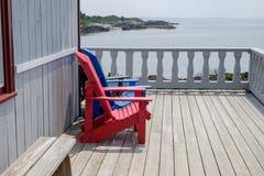 Bunte Plattform- und Strandstühle Adirondack im hellen Rot und im Brigg Lizenzfreie Stockfotos