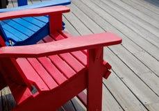 Bunte Plattform- und Strandstühle Adirondack im hellen Rot und im Brigg Lizenzfreie Stockfotografie