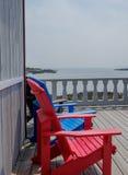 Bunte Plattform- und Strandstühle Adirondack im hellen Rot und im Brigg Stockbilder