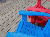 Bunte Plattform- und Strandstühle Adirondack im hellen Rot und im Brigg Lizenzfreies Stockbild