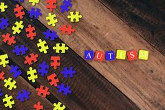 Bunte Puzzle- und Alphabetfliesen mit AUTISMUS-Wort auf Holztisch stockbilder