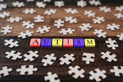 Bunte Puzzle- und Alphabetfliesen mit AUTISMUS-Wort auf Holztisch Stockfotografie