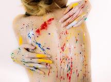 Bunte Rückseite der jungen Frau im Farbengriff selbst durch Hände auf Whit Lizenzfreie Stockfotografie