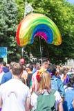 Bunte Regenbogenstolz-Regenschirmleute, die in homosexuelle Parade gehen Stockfoto
