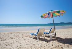 Bunte Regenschirm- und Strandbetten auf Meer Lizenzfreie Stockfotografie