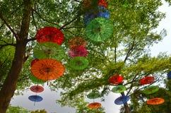 Bunte Regenschirme, die an den Bäumen hängen Lizenzfreies Stockbild