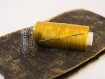 Bunte Rolle des Threads auf einem Stück Leder mit einer Nadel Stockfoto