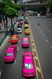 Bunte rosa, gelbe Taxis im Verkehr von Bangkok Stockfotos