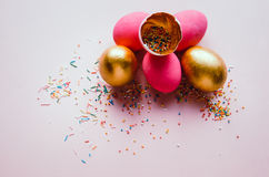 Bunte rosa und goldene Ostereier mit dem Süßigkeitenbesprühen Lizenzfreies Stockfoto