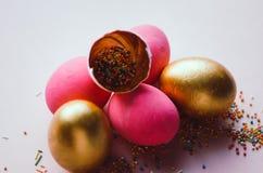 Bunte rosa und goldene Ostereier mit dem Süßigkeitenbesprühen Lizenzfreie Stockfotografie