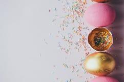 Bunte rosa und goldene Ostereier mit dem Süßigkeitenbesprühen Stockfoto