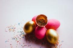 Bunte rosa und goldene Ostereier mit dem Süßigkeitenbesprühen Lizenzfreies Stockbild