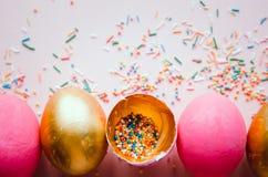 Bunte rosa und goldene Ostereier mit dem Süßigkeitenbesprühen Lizenzfreie Stockbilder