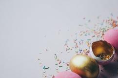 Bunte rosa und goldene Ostereier mit dem Süßigkeitenbesprühen Stockfotos