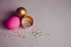 Bunte rosa und goldene Ostereier mit dem Süßigkeitenbesprühen Stockbilder