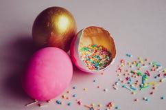Bunte rosa und goldene Ostereier mit dem Süßigkeitenbesprühen Stockbild