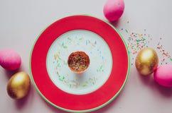 Bunte rosa und goldene Ostereier mit den Süßigkeiten, die auf Platte besprühen Stockbild
