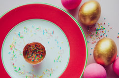 Bunte rosa und goldene Ostereier mit den Süßigkeiten, die auf Platte besprühen Lizenzfreie Stockfotografie