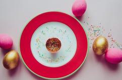 Bunte rosa und goldene Ostereier mit den Süßigkeiten, die auf Platte besprühen Lizenzfreies Stockfoto