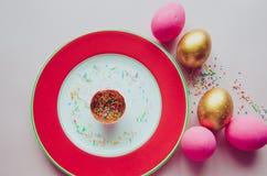 Bunte rosa und goldene Ostereier mit den Süßigkeiten, die auf Platte besprühen Lizenzfreies Stockbild