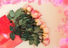 Bunte Rosen in der roten Geschenktasche Stockfotos