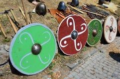 Bunte runde Schilder, helle batlle Äxte, konische Sturzhelme und verschiedene Messer angezeigt auf mittelalterlichem Sommerfestiv Lizenzfreie Stockfotografie