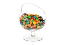 Bunte Süßigkeit fällt in das Glas, das auf Weiß mit Reflexion lokalisiert wird Lizenzfreie Stockbilder