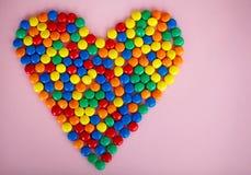 Bunte Süßigkeit in Form von Herzen auf dem rosa Hintergrund diff lizenzfreie stockfotos