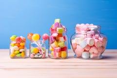 Bunte Süßigkeit im Glas auf Tabelle mit blauem Hintergrund Lizenzfreie Stockbilder