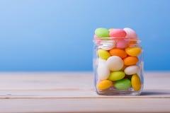Bunte Süßigkeit im Glas auf Tabelle mit blauem Hintergrund Lizenzfreie Stockfotos