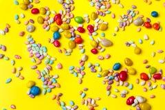 Bunte Süßigkeiten auf gelbem Hintergrund Flache Lage lizenzfreie stockfotos