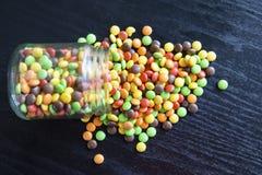 Bunte Süßigkeiten mit einem Glas stockfotos