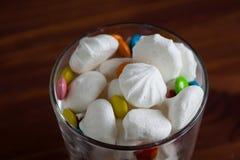 Bunte Süßigkeiten und Bonbons, Meringe in einem Glas auf einem hölzernen BAC Stockfotografie