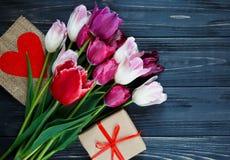 Bunte schöne Tulpen und Geschenkbox auf dem grauen Holztisch Valentinsgrüße, Frühlingshintergrund Blumenspott oben mit copyspace lizenzfreies stockfoto