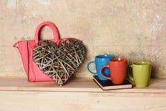 Bunte Schalen auf Buch und großem hölzernem braunem Herzen mit Handtasche der rosa Damen auf Textur- und hölzernem Hintergrund de stockbild