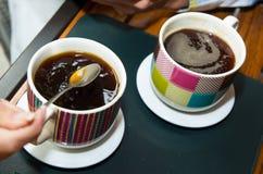 Bunte Schalen der Nahaufnahme zwei coffe an sitzend Stockfoto