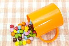 Bunte Schokolade und Becher Stockbild