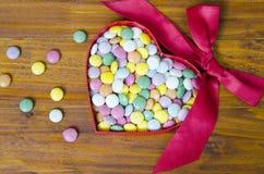 Bunte Schokoladenpillen in einem Herzen formten Kasten Stockbild
