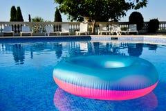 Bunte Schwimmweste, die in ein haarscharfes Pool schwimmt Lizenzfreies Stockbild