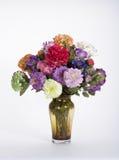 Bunte Silk Zinnias, Gartennelken und tiefrosa Rose in bernsteinfarbigem G Stockbild