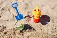 Bunte Sommerstrandspielwaren, -eimer, -berieselungsanlage und -schaufel auf Sand Stockfoto